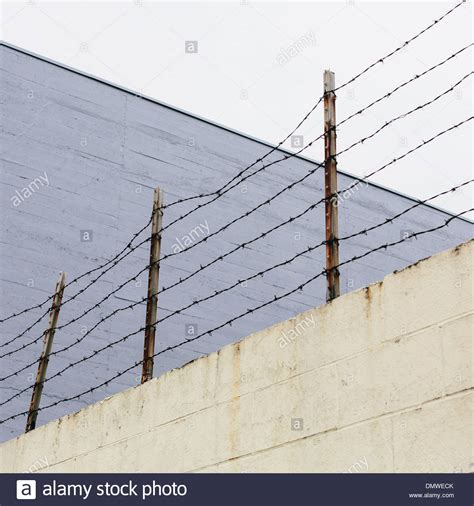barbed wire fence at top of a wall in a city stock photo