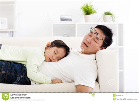 sleeping in asia father and daughter sleeping on the sofa stock photo