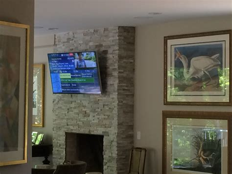 flat panel tv mounted to a stone facade with a tilt mount
