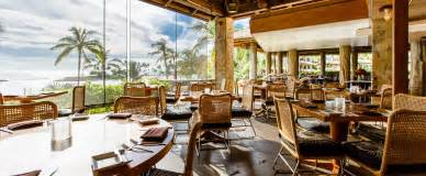 Tables on a covered patio look upon palm trees and ocean views through