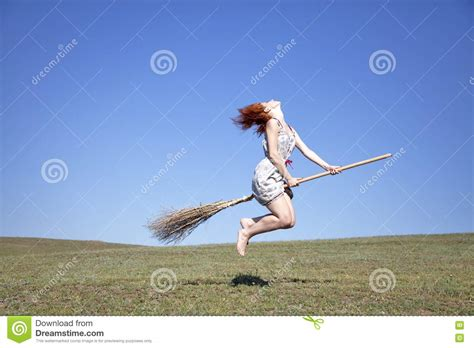 flying on haired witch on broom flying green stock