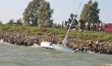 buitenboordmotor enkhuizen twee zeiljachten op de keien gestrand bij oosterleek
