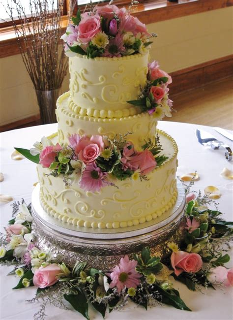 pink lavender 3 tier wedding cake with fresh color flowers scrollwork on sides