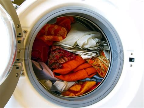 how to wash colors in washing machine washing machine with colored clothes laundry stock photo