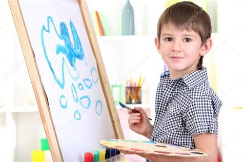 painting for boy boy painting paints picture on easel stock photo