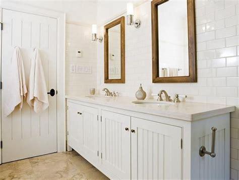 Crisp white cottage beachy bathroom design with white beadboard bathroom cabinets vanity double