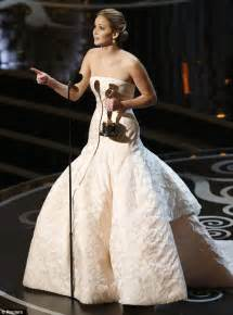Jennifer lawrence trips and falls as she climbs steps to accept her