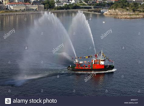 Tug Boat Shoppinf tug boat spraying water as a send for cruise ship stock photo royalty free image