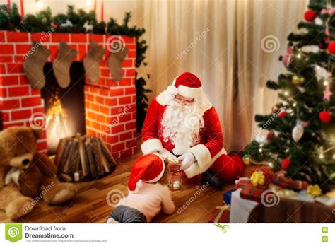 Santa Claus In House by Santa Claus On The Floor In The House Gives Gifts To The