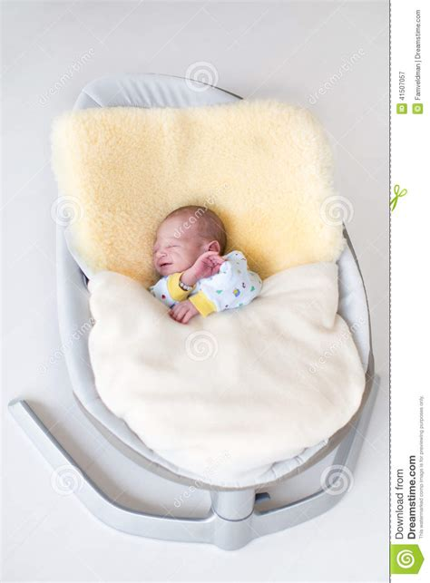 baby sleeping in swing sweet newborn baby boy in swing on a sheepskin stock photo
