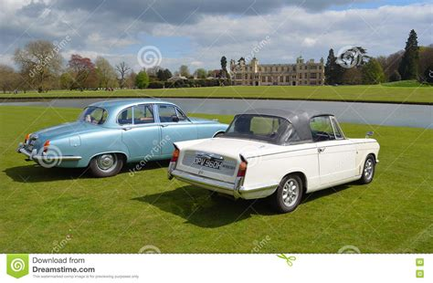 two classic cars in front of stately home a triumph