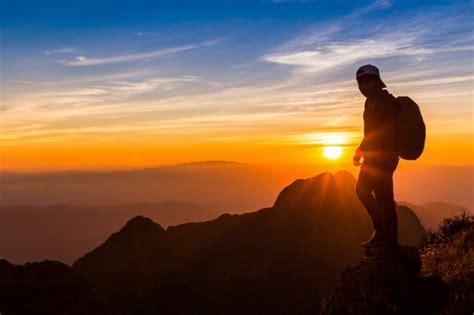 silueta de  hombre en la cima de una montana silueta de