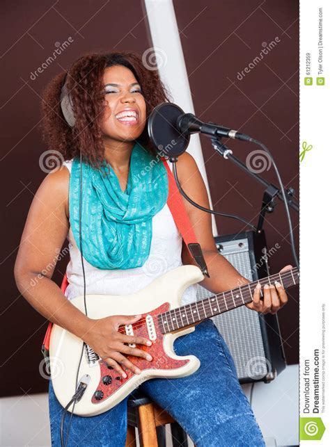 who is the singer playing guitar in the direct tv commercial may 2016 female singer playing guitar in recording studio stock