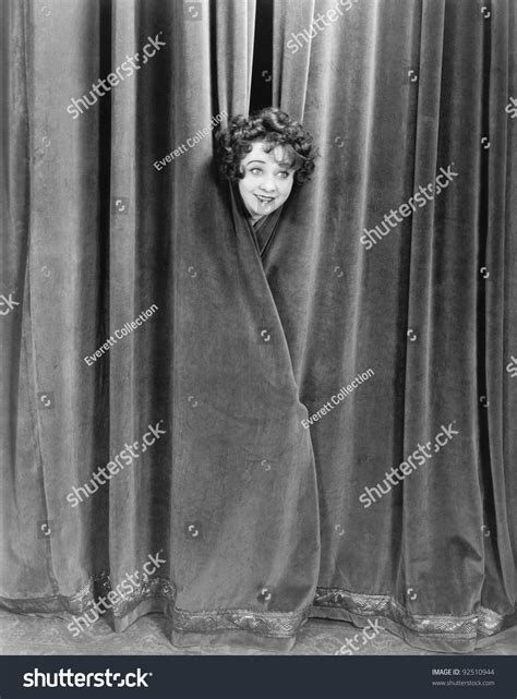 woman behind the curtain woman peek a booing behind a curtain stock photo 92510944