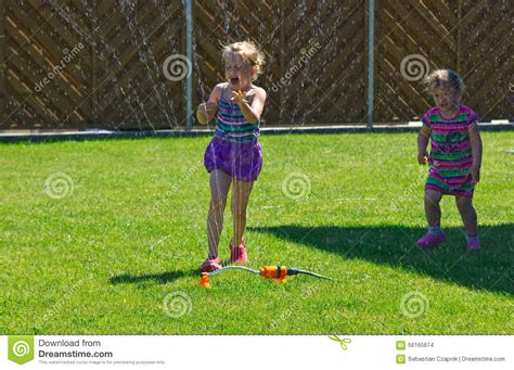 backyard babes girls having fun with sprinkler in garden stock photo