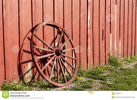 Cabin Building Plans old rustic wagon wheel beside a red barn stock image