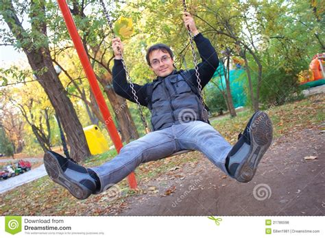 swing man young smiling man on swing royalty free stock photos