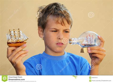 boy and boy holds model of sailing ship and ship in bottle stock