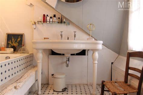 Ancien lavabo en faïence blanche sur pieds, carrelage