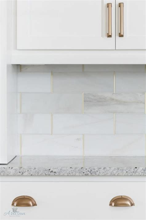 honed white tiles with gold trim transitional kitchen