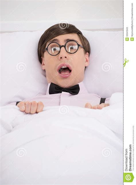 nerdy bedding terrified nerd scared nerd lying on the bed and looking at came stock photos image