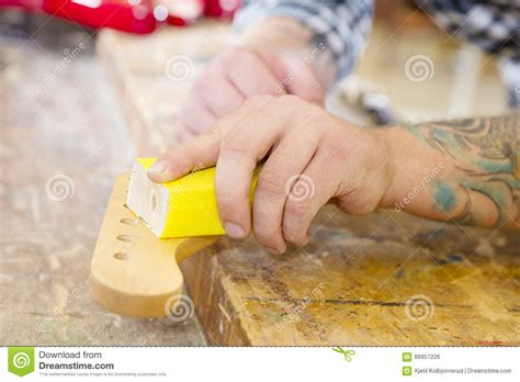 working man tattoo carpenter sanding a guitar neck in wood at workshop stock