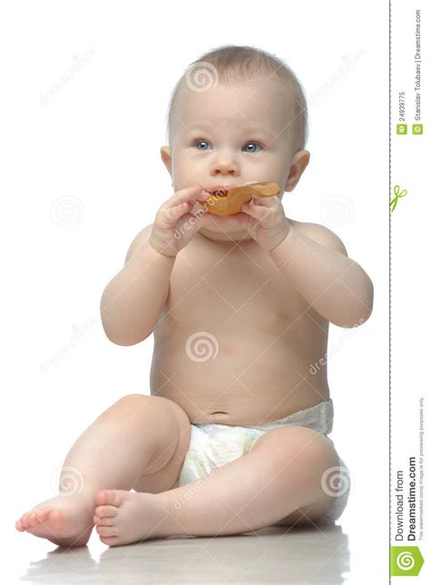 a small child in a nappy plays with the lock to a beach hut on the toddler in diaper playing with wodden spoon stock image