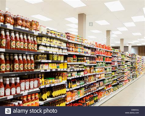 stocked shelves in grocery store aisle stock photo