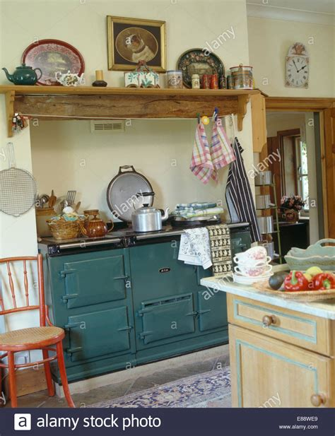 Wooden Country Kitchen by Wooden Shelf Above Green Aga In Traditional Country Kitchen Stock Photo Royalty Free Image