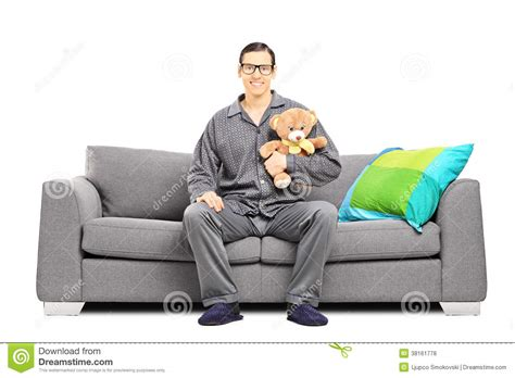 sitting in sofa young man in pajamas sitting on sofa with teddy bear