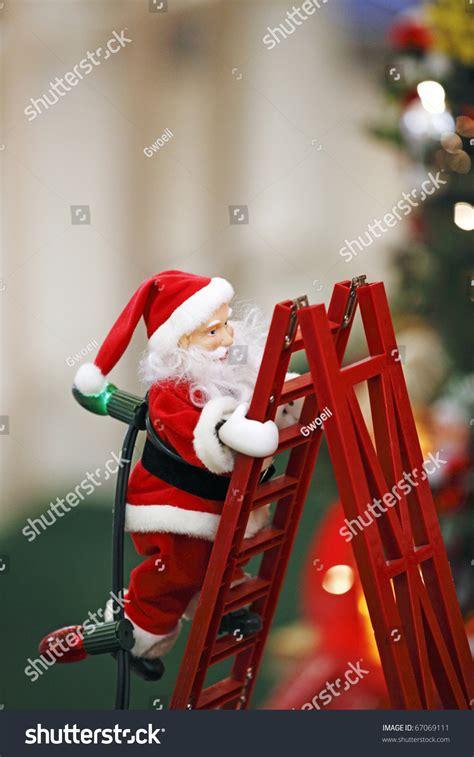 climbing santa ladder christmas decoration santa claus climbing ladder carrying stock photo 67069111