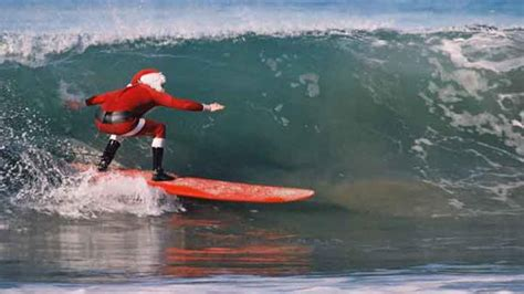 santa on surfboard surfing santa rides the season s waves in the south bay ktla