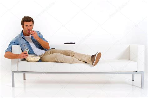 watching tv on couch single man on the couch watching tv stock photo