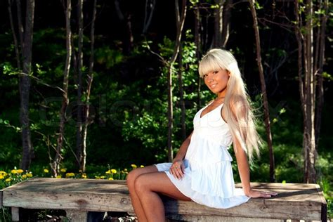 0008288607 the girl in the woods girl in white dress sitting on a bench in the woods