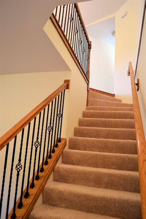 wood handrail w decorative metal spindles carpeted