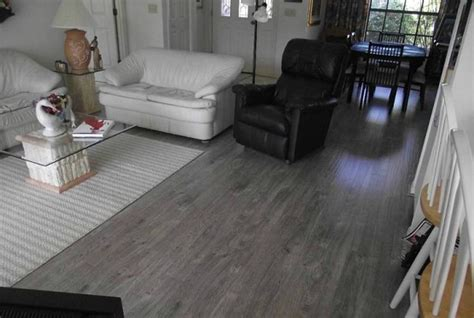 Dark grey laminate flooring in living room with black and