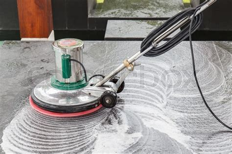 Thai people cleaning black granite floor with machine and