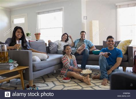 family in living room family watching tv with popcorn in living room stock photo