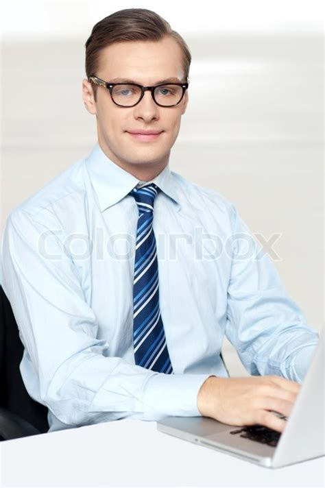 man sitting on chair using laptop in office stock photo