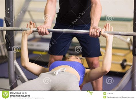 women bench pressing trainer helping woman to lift the barbell bench press in gym stock photo image 37387598