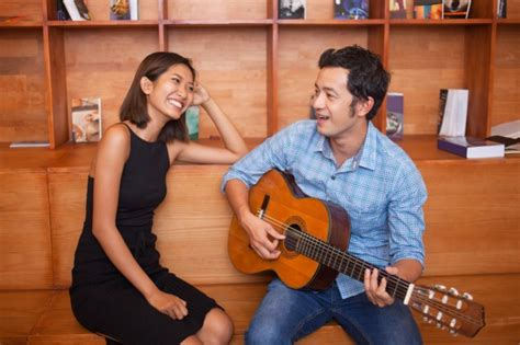 male singer with guitar on direct tv commercial man singing and playing guitar for smiling woman photo