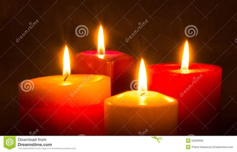 four colored candles burning in the stock photo