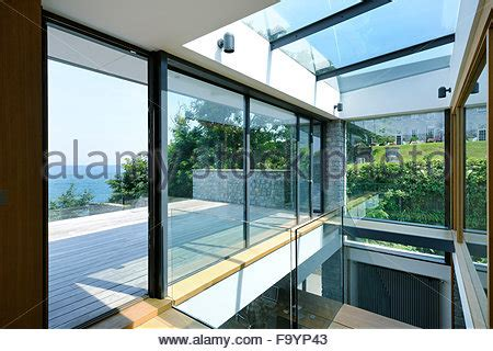 floor to ceiling glass panels glazed atrium and staircase in residential house uk stock