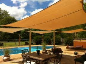 installing outdoor sun shade sails over a pool