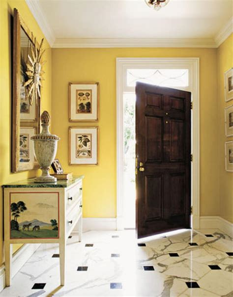 Yellow Wall Paint Color With Wooden Door And Foyer This