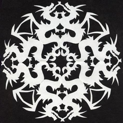 paper cut out pattern dragon pattern snowflake cutouts and printer paper on