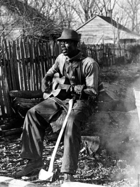 A young African-American sharecropper playing the guitar