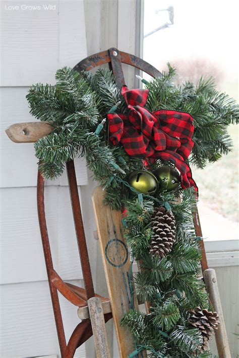 rustic holiday porch decor snow sled pinecone and greenery