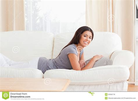 lying on a sofa young woman lying on sofa royalty free stock photos