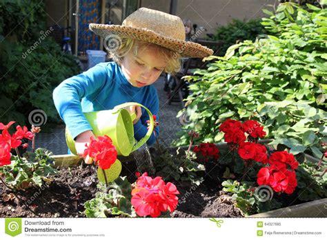 innaffiare giardino bambino piccolo innaffia i fiori nel giardino immagine